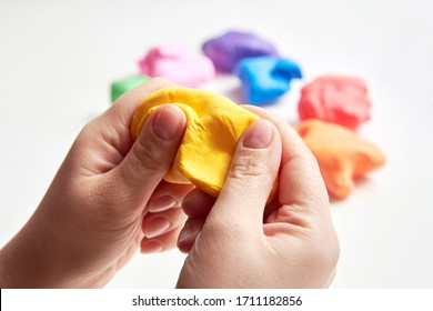 The hand of a girl who sculpts from light airy multi-colored plasticine, developing activities.
