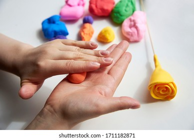 The hand of a girl who sculpts roses from light airy multi-colored plasticine, developing activities.