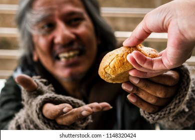 Hand giving bread or food to blurred happy face homeless male