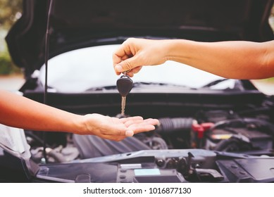 Hand giving car key on car background at garage,helping concept.