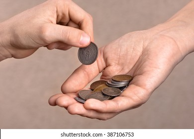 hand giving a coin to another person