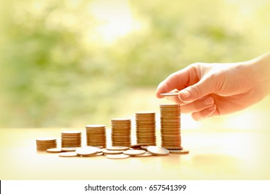 Hand giving coins into stack, business and finance concept