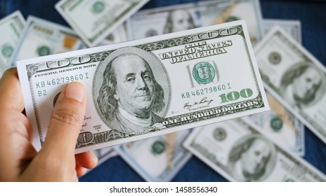 Hand giving dollars cash close up against blurred 100 dollars bank note money background, tax payment or economic system and business financial loans concept.