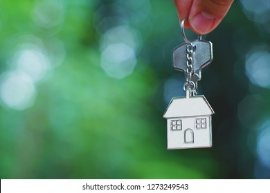 Hand giving home key with love house keyring with blur green garden, background, sweet home concept, copy space