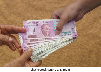 Hand Giving Indian 500 and 2000 Rupee Bank Notes over wheat background. concept for earnings or spend in Agriculture.
