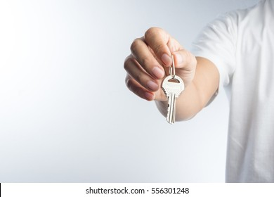 Hand giving keys on white background