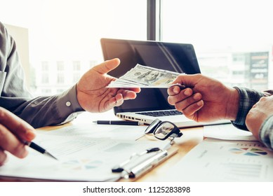 Hand giving money - United States Dollars . Hand receiving money from businessman.corruption concept