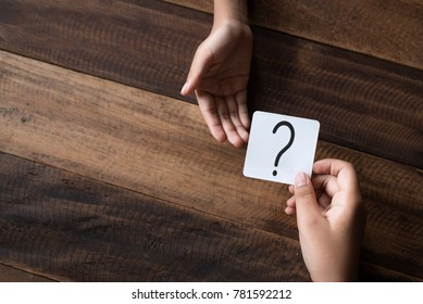 hand giving a note written question mark. asking question concept