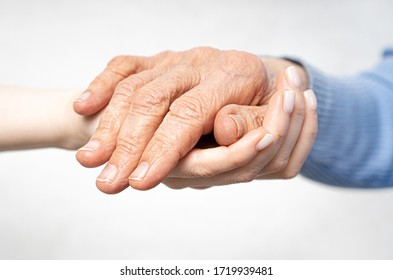 Hand giving for old woman. Young hands hold old hands. Support for the elderly concept.