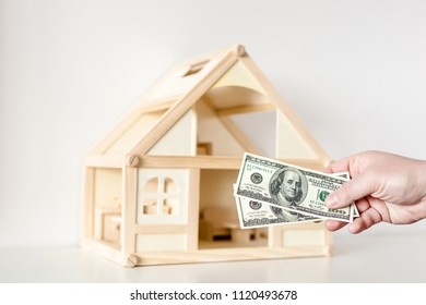 Hand giving one hundred us dollar banknotes. Wooden house model on background. Real estate investment.Bargain or deal concept