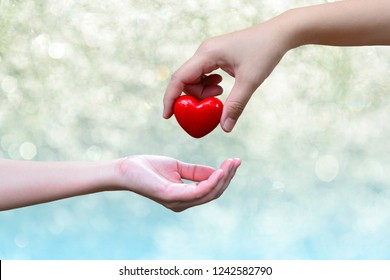 A hand giving a red heart to hand for concept donation and philanthropy