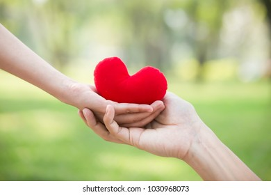 Hand giving red heart to hand. Love , health care , health insurrance concept.