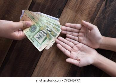 Hand giving Saudi Riyal bank notes. donate and charity concept
