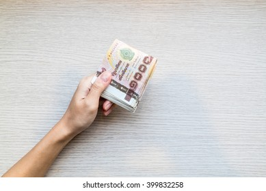 Hand giving stack of thousand bath Thai money with copy space