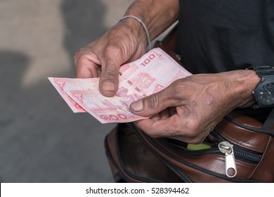 Hand giving Thai banknotes