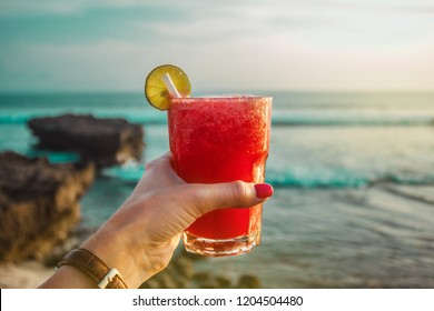 Hand with glass of cocktail with watermelon juice on the background of the ocean. Sunset on the sea. Healthy red drink. Bali, Indonesia, Canggu, Echo beach. Vacation time