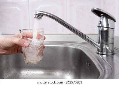 Hand with glass of water poured from kitchen faucet
