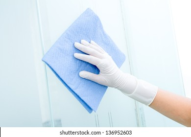 Hand with glove and blue sponge cleaning the bathroom glass