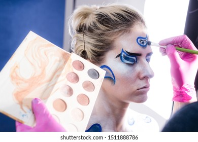 Hand in glove with brown palette to makeup. Professional body art artist at work. Makes a body art. Body painting in process