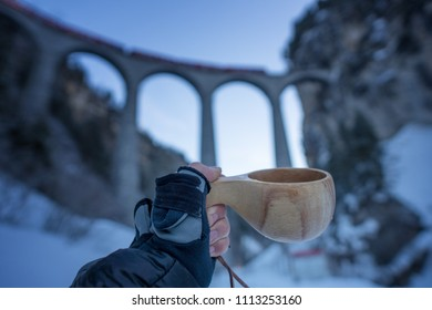 Hand with glove holding wooden cup in cold setting in front of Landwasser Viaduct in Filisur Graubünden Switzerland that is crossed by train