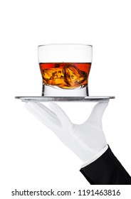 Hand with glove holds tray with glass of whiskey and ice cubes on white background