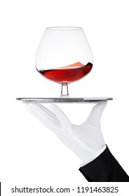 Hand with glove holds tray with glass of brandy cognac on white background