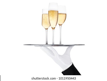 Hand with glove holds tray with glasses of yellow champagne with bubbles on white background with reflection