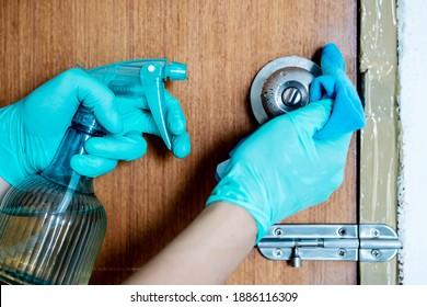 Handschuhe, die Türknauf mit Alkoholspray reinigen. Schutz durch Corona-Virus oder Bakterien.