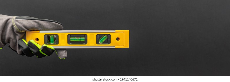 Hand in gloves holds a yellow building level on a black background. Postcard or poster for print, place for text - Shutterstock ID 1941140671