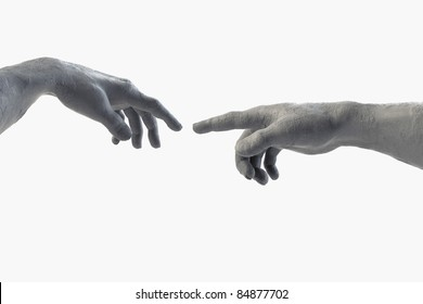 Hand of God and Adam made of sculpting clay on white