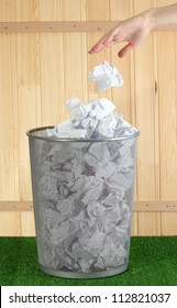 hand going garbage in metal trash bin from paper on grass on wooden background