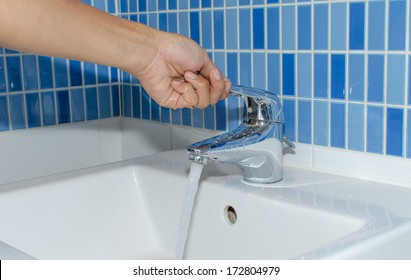 Hand is going to open a faucet the waters to flow.