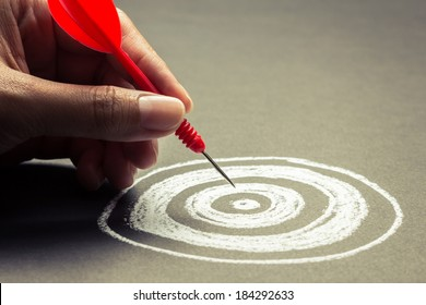 Hand going to take dart into the center of sketching dartboard