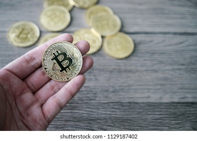 hand with golden bitcoin coin on the wooden table