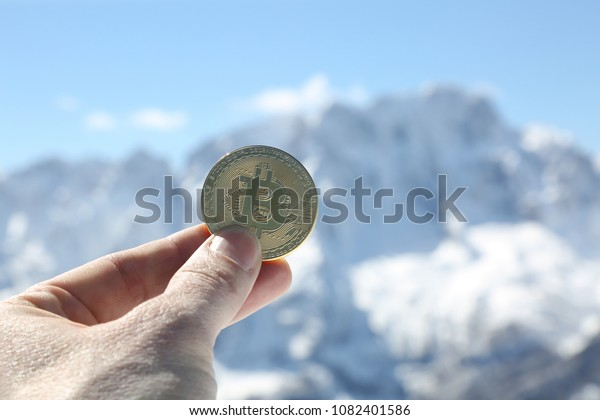 hand with a golden bitcoin and mountains on background