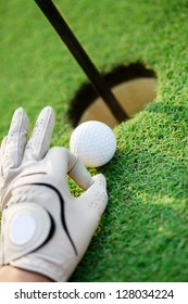 Hand with golf gloves cheating, pulling the ball into the hole
