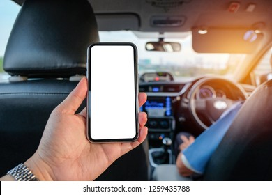 Hand grab smartphone to use internet on mobile app in back seat taxi