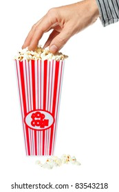 A hand grabbing delicious popcorn out of a container. Isolated over white.