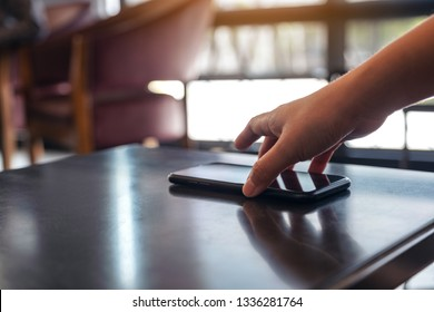 A hand grabbing and picking up mobile phone on the table