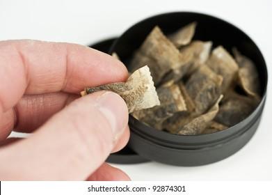 A hand grabbing a pinch of snuff