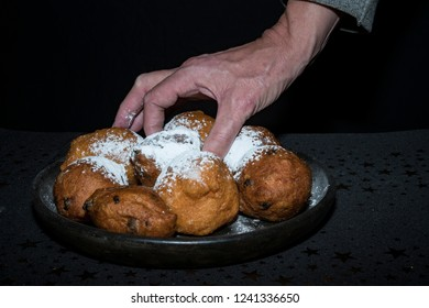 hand grabs oliebollen, oil dumpling or fritter, in paper bag, for Dutch New Year's Eve