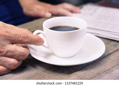 Hand grap white coffee cup on working table with background business man is reading newspaper.