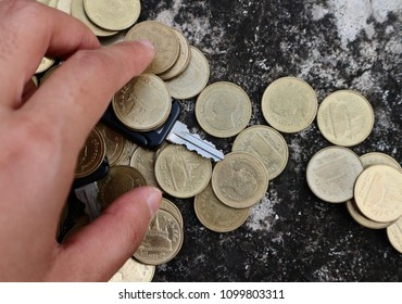 Hand grasp key under gold coin money on dirty cement stone floor