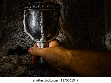 Hand grasping goblet containing a potion.