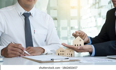 The hand grasping the home design of the real estate agent provides the homeowner design. Successful business contract concept