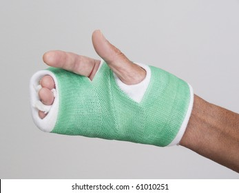 Hand in green cast which covers palm and three fingers. Protection after bone surgery. Gray background.