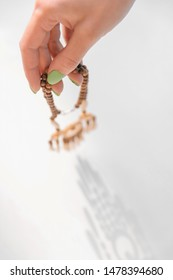 Woman's hand with green manicure holding wooden handcraft necklace. Shadow on a white background.