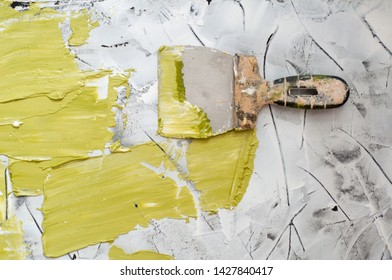 Hand with green olive putty knife repair wall, Hand with a spatula, spatula with spackle paste structure, process of applying layer of putty trowel. Copy space