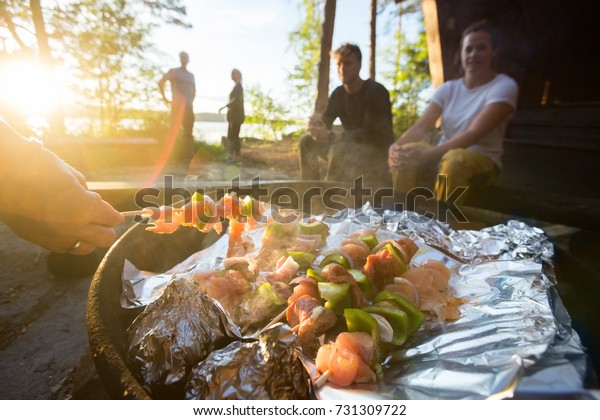 Hand Grilling Food On Skewers With Friends In Background