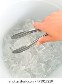 Hand grip ice cube in bucket.